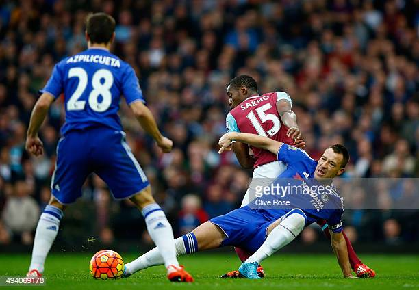 John Terry of Chelsea and Diafra Sakho of West Ham United compete for the ball during the Barclays Premier League match between West Ham United and...