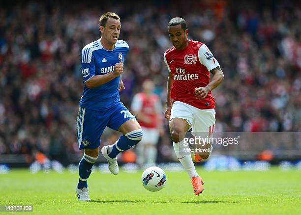 John Terry of Chelsea and Theo Walcott of Arsenal compete for the ball during the Barclays Premier League match between Arsenal and Chelsea at...