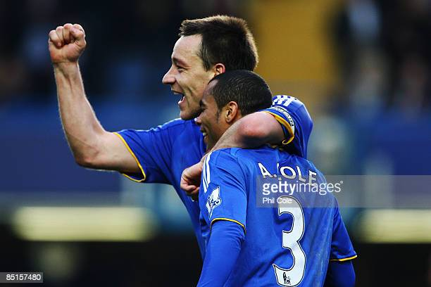 John Terry of Chelsea celebrates with team mate Ashley Cole following the Barclays Premier League match between Chelsea and Wigan Athletic at...