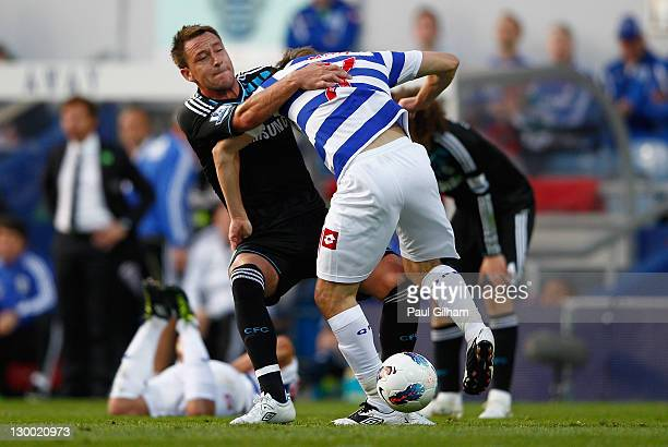 John Terry of Chelsea grapples Tommy Smith of Queens Park Rangers to the ground during the Barclays Premier League match between Queens Park Rangers...