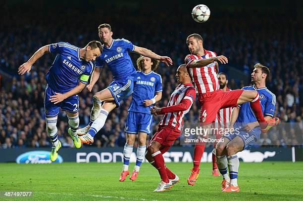 John Terry of Chelsea heads clear as he is closed down by Mario Suarez of Club Atletico de Madrid during the UEFA Champions League semifinal second...