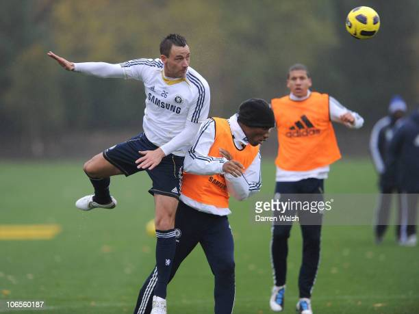 John Terry of Chelsea heads past Didier Drogba during a training session at the Cobham training ground on November 5, 2010 in Cobham, England.