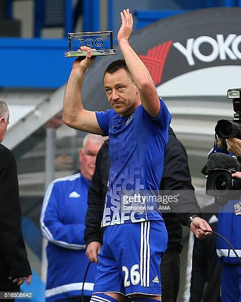 John Terry of Chelsea is presented with a plaque to mark 700 appearances for the club ahead of the Barclays Premier League match between Chelsea and...