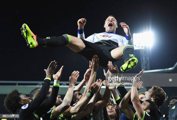 John Terry of Chelsea is thrown in the air by team mates while celebrating winning the league title after the Premier League match between West...