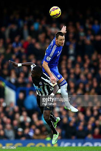 John Terry of Chelsea jumps for the ball with Moussa Sissoko of Newcastle United during the Barclays Premier League match between Chelsea and...