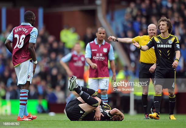 John Terry of Chelsea lies injured after being fouled by Christian Benteke of Aston Villa who is then sentoff by referee Lee Mason during the...