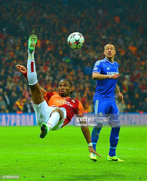 John Terry of Chelsea looks on as Didier Drogba of Galatasaray clears the ball during the UEFA Champions League Round of 16 first leg match between...