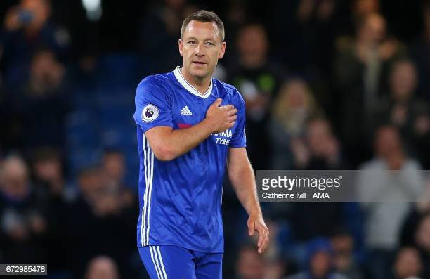 John Terry of Chelsea pats the chelsea badge on his shirt as the crowd chant his name after the Premier League match between Chelsea and Southampton...