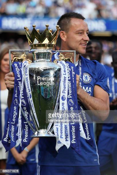 John Terry of Chelsea poses with his winners medal and the Premier League trophy at the end of the Premier League match between Chelsea and...