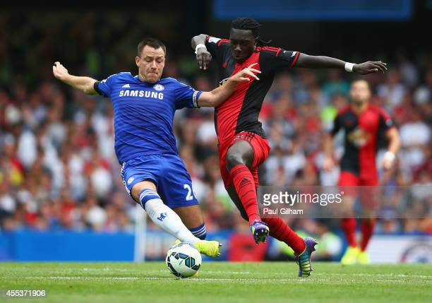 John Terry of Chelsea tackles Bafetibis Gomis of Swansea City during the Barclays Premier League match between Chelsea and Swansea City at Stamford...
