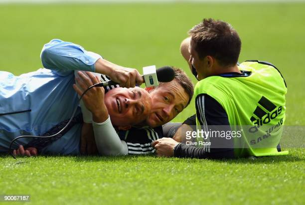 John Terry of Chelsea wrestles with a TV presenter during a training session at Stamford Bridge on August 25 2009 in London England