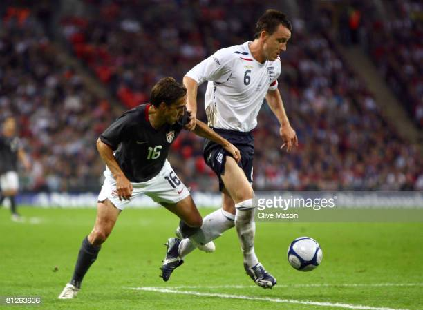 John Terry of England holds off Josh Wolff of USA during the international friendly match between England and the USA at Wembley Stadium on May 28...