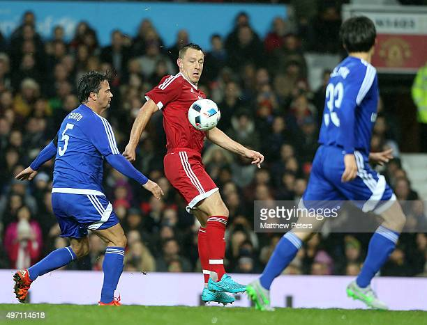 John Terry of Great Britain and Ireland in action with Fernando Couto and Jisung Park of Rest of the World during the David Beckham Match for...