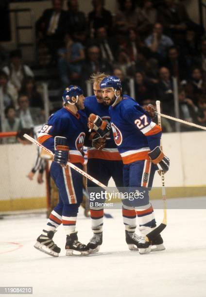 John Tonelli Butch Goring and Bob Nystrom of the New York Islanders celebrate a goal during their game circa 1979