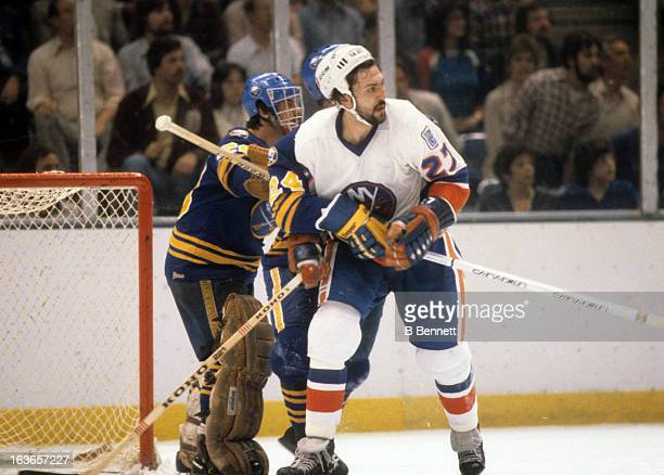 John Tonelli of the New York Islanders battles with goalie Bob Sauve and Bill Hajt of the Buffalo Sabres during the 1980 Semi Finals in May 1980 at...