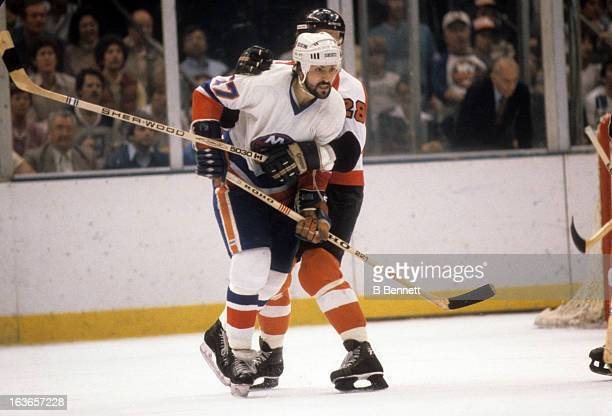 John Tonelli of the New York Islanders battles with Mike Busniuk of the Philadelphia Flyers during the 1980 Stanley Cup Finals in May 1980 at the...