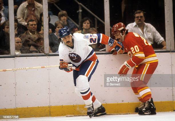 John Tonelli of the New York Islanders skates away from a check from Bob Murdoch of the Atlanta Flames on October 16 1979 at the Nassau Coliseum in...