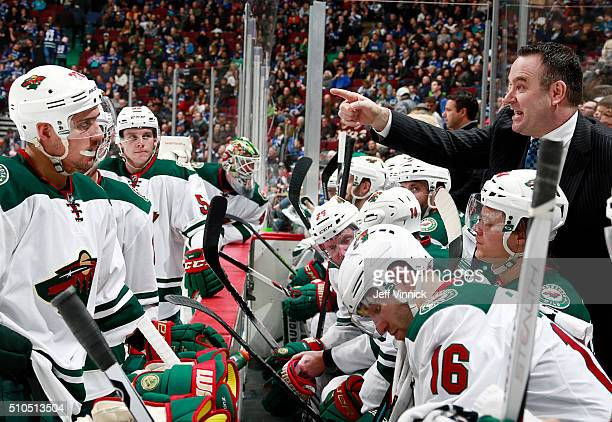 John Torchetti provides instruction during his first game as head coach of the Minnesota Wild during the NHL game against the Vancouver Canucks at...
