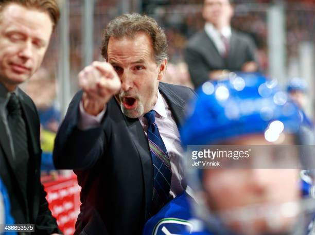 John Tortorella of the Vancouver Canucks shouts at the Calgary Flames' bench during their NHL game at Rogers Arena January 18 2014 in Vancouver...