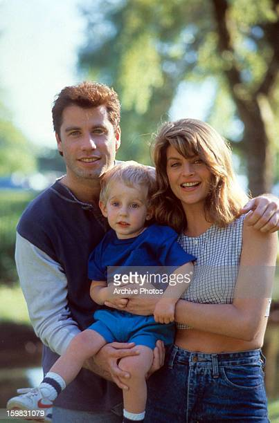 John Travolta and Kirstie Alley holding a child in a scene from the film 'Look Who's Talking' 1989