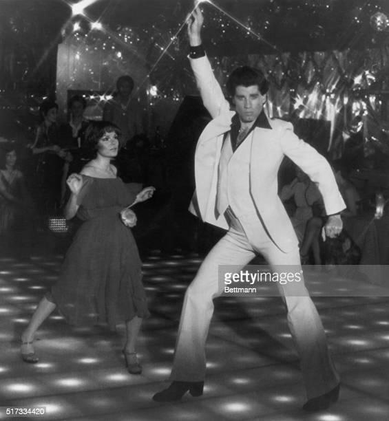 John Travolta as Tony Manero in his famous discodancing pose in Saturday Night Fever His dance partner is actress Karen Lynn Gorney