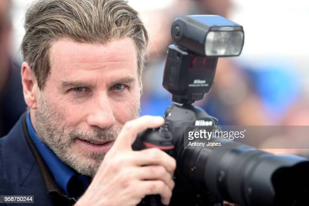 John Travolta borrows a camera to take pictures at the photocall for 'Rendezvous With John Travolta Gotti' during the 71st annual Cannes Film...