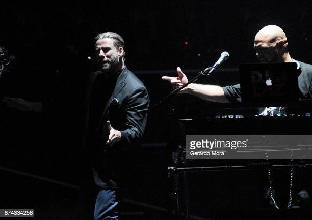 John Travolta makes a quick appearance on stage before Pitbull show at the Amway Center on November 14 2017 in Orlando Florida