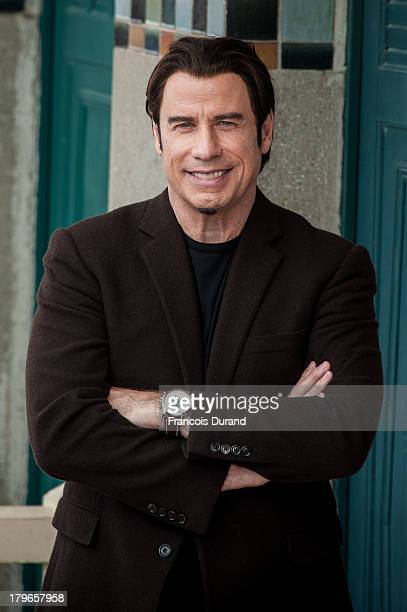 John Travolta poses next to the beach closet dedicated to him during a photocall on the Promenade des Planches during the 39th Deauville American...