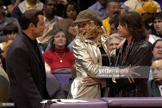 John Travolta watches Uma Thurman admire Stephen Tyler during the first half of action at the Los Angeles Lakers versus Sacramento Kings game on...
