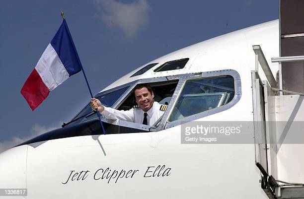 John Travolta, who recently completed a pilot training course with airline Qantas, waves the French flag from the cockpit of the actor's vintage...