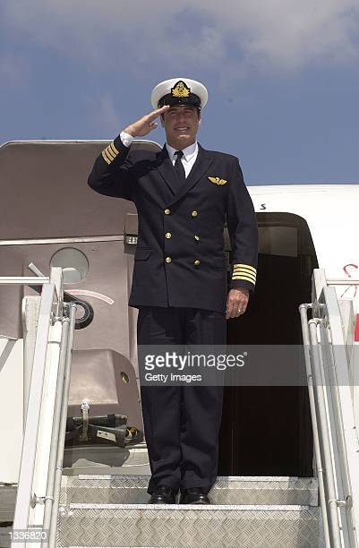 John Travolta, who recently completed a training course with airline Qantas, salutes in front of the actor's vintage Boeing 707 August 13, 2002 in Le...