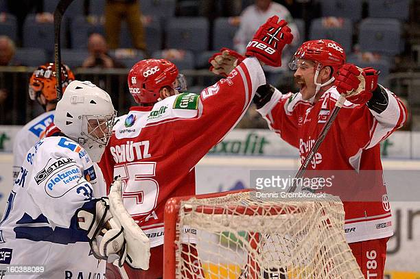 John Tripp of Cologne celebrates with teammates after scoring the winning goal during the DEL match between Koelner Haie and Iserlohn Roosters at...
