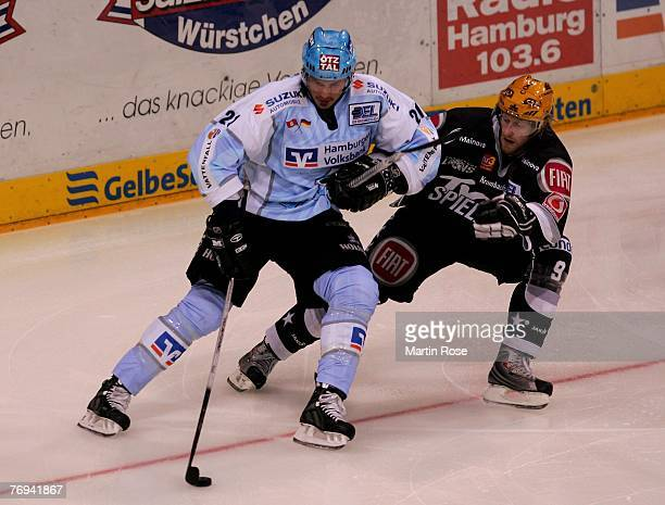 John Tripp of Hamburg and Lasse Kopitz of Frankfurt fight for the puck during the DEL match between Hamburg Freezers and Frankfurt Lions at the Color...