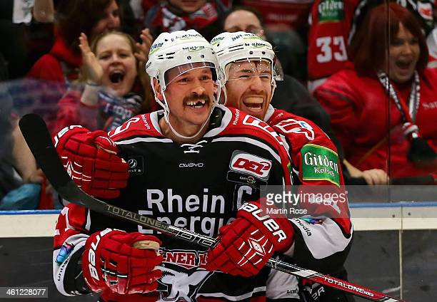 John Tripp of Koeln celebrate with tem mate Bjoern Krupp after he scores his team's winning goal in over time during the DEL match between Koelner...
