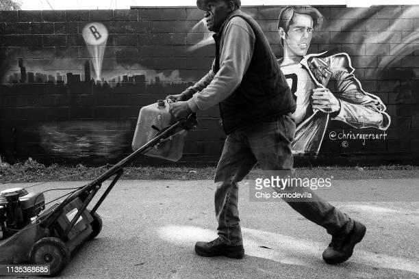 John Truitt of Black and Gold Landscape walks past a mural depicting US Senate candidate Rep Beto O'Rourke November 1 2018 in Austin Texas Community...