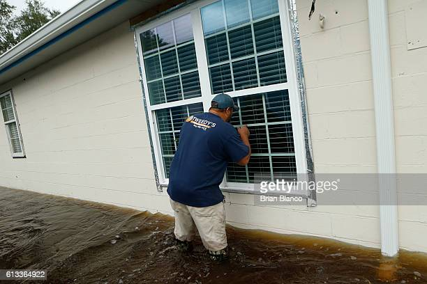 John Tweedy looks through a window as he wades into the swiftmoving floodwater surrounding his business as he inspects damage in the wake of...