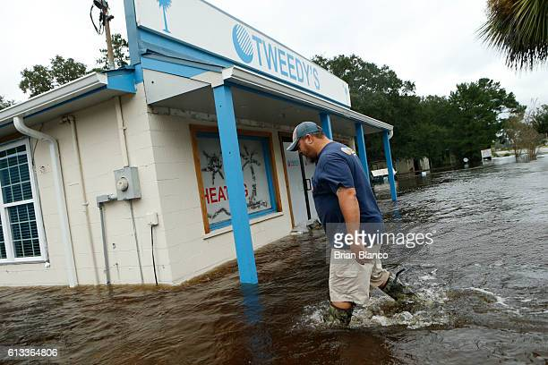 John Tweedy wades into the swiftmoving floodwater surrounding his business as he inspects damage in the wake of Hurricane Matthew on October 8 2016...