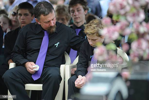 John Tyson sits next to his son Blake Tyson as they mourn at the funeral of family members Donna Maree Rice and son Jordan Rice killed in last week's...
