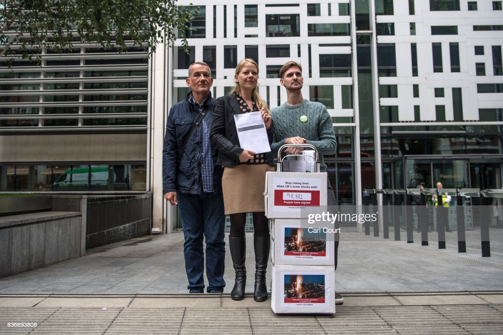 John Tyson (R), the founder of a petition to bring in fire safety regulations to make Britain's tower blocks safer, poses for a photograph with Sian Berry, the Leader of the Green Party in the London Assembly (C) and Dave Lewis, from the Lakanal House residents group, before handing in the petition to the Department for Communities and Local Government on August 22, 2017 in London, England. The list of 99,274 signatures to the DCLG follows the critical findings of the 2013 coroner's report on the 2009 Lakanal fire, which highlighted issues that could have prevented Grenfell, the petition is asking for the immediate implementation of recommendations from that report.