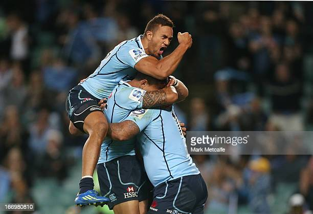 John Ulugia of the Waratahs celebrates scoring a try with teammates Israel Folau and Peter Betham during the round 10 Super Rugby match between the...
