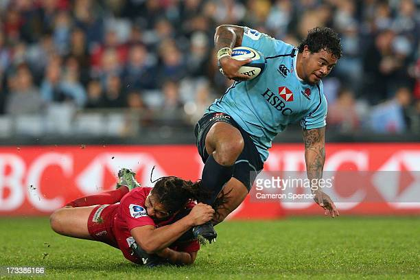 John Ulugia of the Waratahs is tackled during the round 20 Super Rugby match between the Waratahs and the Reds at ANZ Stadium on July 13, 2013 in...