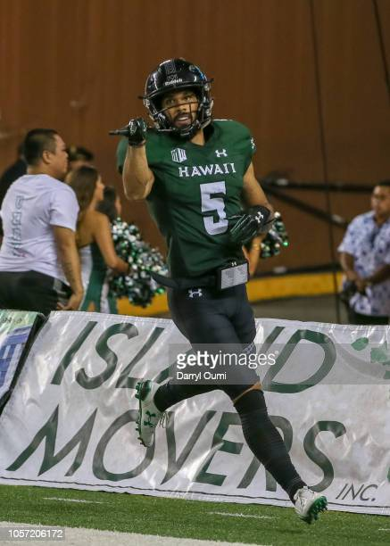 John Ursua of the Hawaii Rainbow Warriors gestures his teammates after scoring a touchdown during the third quarter against the Utah State Aggies at...