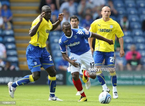 John Utaka of Portsmouth battles with Seyi Olifinjana of Cardiff City during the npower Championship match between Portsmouth and Cardiff City at...