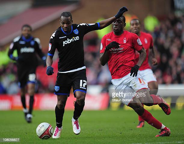 John Utaka of Portsmouth breaks away from Guy Moussi of Nottingham Forest during the npower Championship match between Nottingham Forest and...