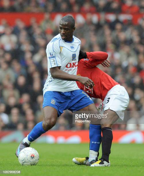 John Utaka of Portsmouth is challenged by Patrice Evra of Manchester United during the FA Cup Sponsored by E.on Quarter Final match between...