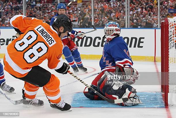 John Vanbiesbrouck of the New York Rangers makes a save against Eric Lindros of the Philadelphia Flyers during the Alumni Game prior to the 2012 NHL...