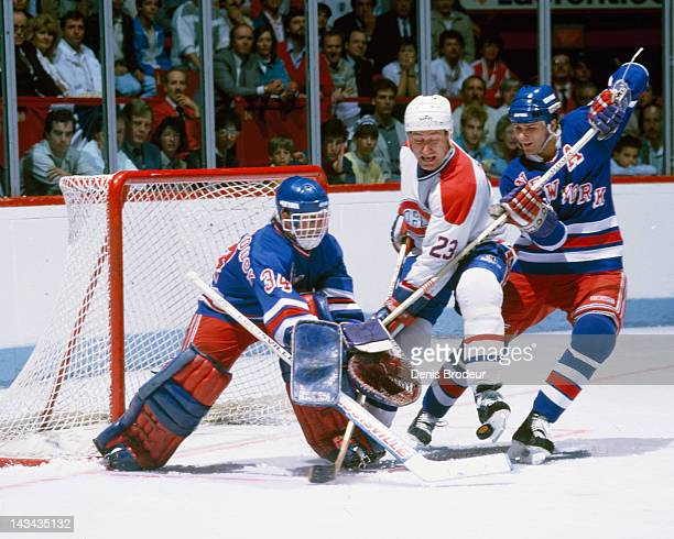 John Vanbiesbrouck of the New York Rangers pokes the puck away from Bob Gainey of the Montreal Canadiens Circa 1990 at the Montreal Forum in Montreal...