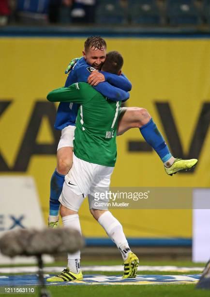 John Verhoek and Goalkeeper Markus Kolke of Hansa Rostock celebrate after scoring during the 3 Liga match between Hansa Rostock and Eintracht...