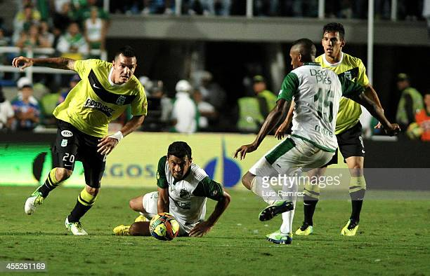 John Viafara and Andres Perez of Deportivo Cali fights for the ball with Alejandro Bernal of Atletico Nacional during the match between and Deportivo...