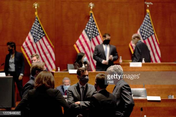 John W Elias a prosecutor in the US Justice Department's antitrust division talks with members of his staff at a hearing of the House Judiciary...